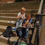 Kinder auf Treppe lesen ein Buch.