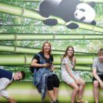 Kinder und Erzieherin sitzen auf Bambus. Im Hintergrund Panda.